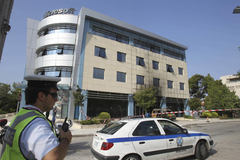 A policeman stands in front of Microsoft's offices in northern Athens, Wednesday, June 27, 2012. Assailants attacked the offices of Microsoft early Wednesday, driving a van through the front doors and setting off an incendiary device that burned the building entrance, police said. (AP Photo/Thanassis Stavrakis)