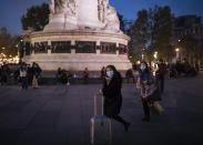 Tourists wearing protective masks walk on Republique square in Paris, Thursday, Oct. 29, 2020. France prepared to shut down again for a month to try to put the brakes on the fast-moving coronavirus. Schools are allowed to remain open in this new lockdown, which is gentler than what France saw in the spring. But still a shock to restaurants and other businesses ordered to close their doors in one of the world's biggest economies.(AP Photo/Lewis Joly)
