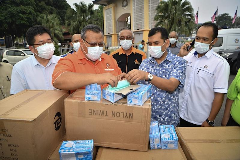 Johor Education, Human Resource, Science and Technology Committee chairman Aminolhuda Hassan examines some of the 50,000 face masks that will be distributed to schools in Tangkak and Muar, in Tangkak September 14, 2019. — Bernama pic