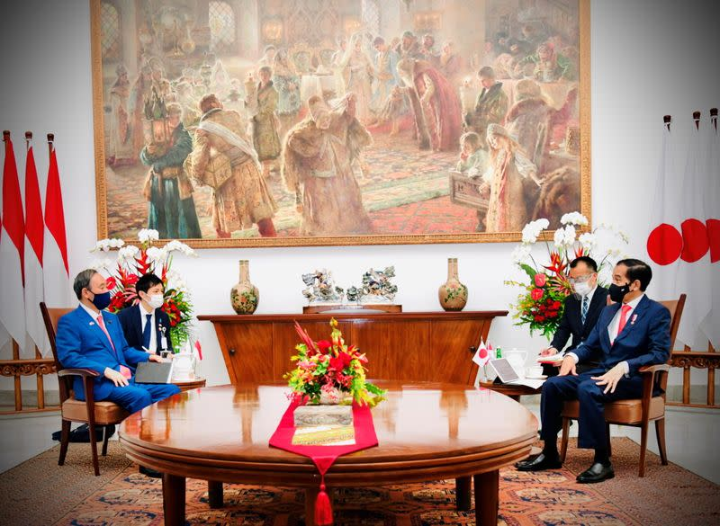 Japan's Prime Minister Suga talks with Indonesian President Widodo during his visit at the Indonesian Presidential Palace in Bogor