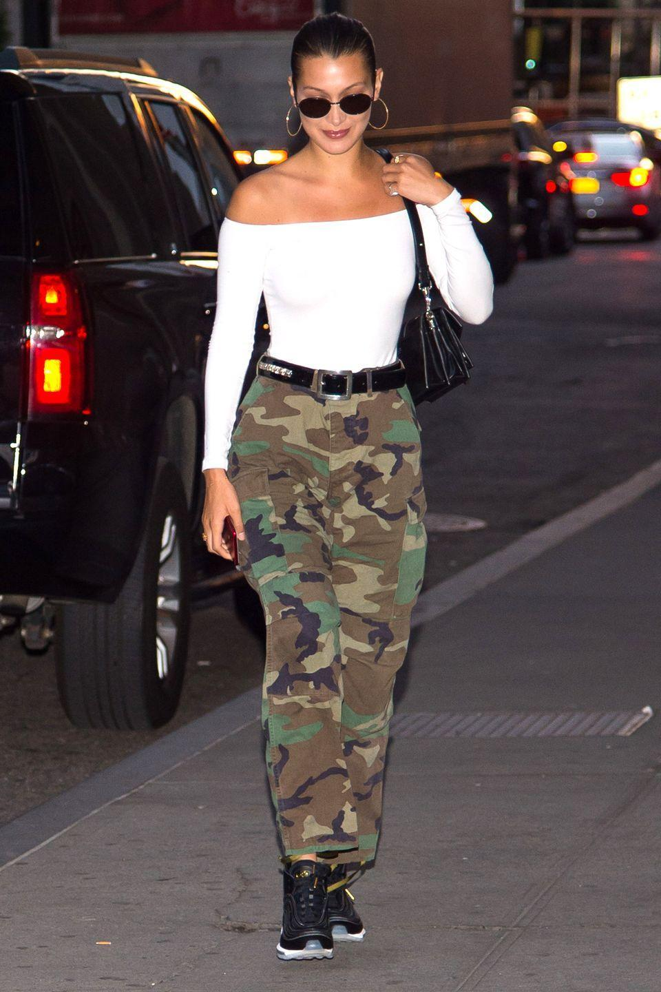 <p>In a white off-the-shoulder bodysuit, camo pants, black high top sneakers, a Chrome Hearts x Bella belt and gold hoops while out to dinner with family in NYC. </p>