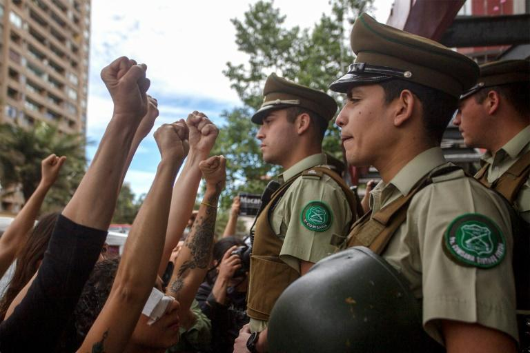 Police guarding the presidential palace in Santiago remained impassive when faced with protests by a group of around a thousand women (AFP Photo/CLAUDIO REYES)