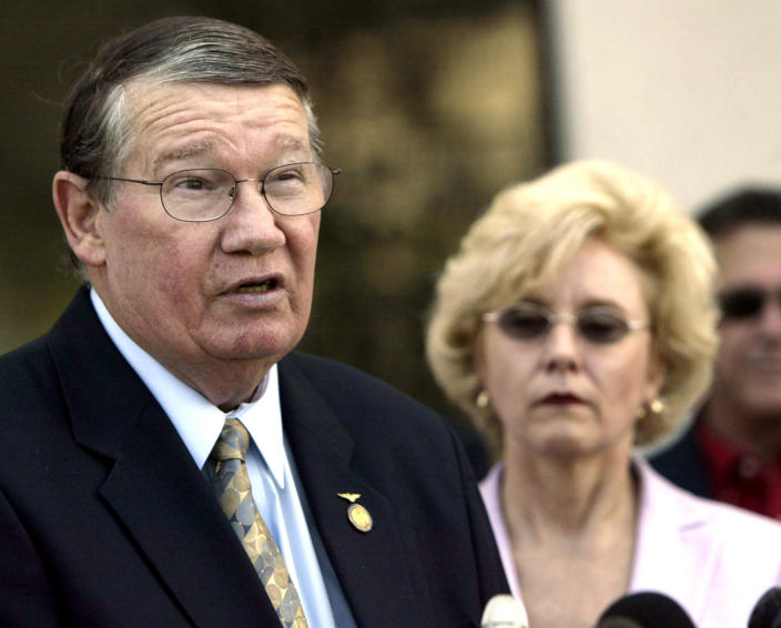 "FILE - In this July 14, 2005, file photo, then-Rep. Randy ""Duke"" Cunningham, flanked by his wife Nancy, announces he will not seek re-election, during a news conference in San Marcos, Calif. When Rep. Cunningham admitted in 2005 to accepting $2.4 million in illegal gifts from defense contractors in exchange for government contracts and other favors, it was considered the largest bribery scandal in congressional history. The disgraced former San Diego congressman received one of the pardons issued Wednesday, Jan. 20, 2021, by President Donald Trump in the final hours of his term. (AP Photo/Lenny Ignelzi, Files)"
