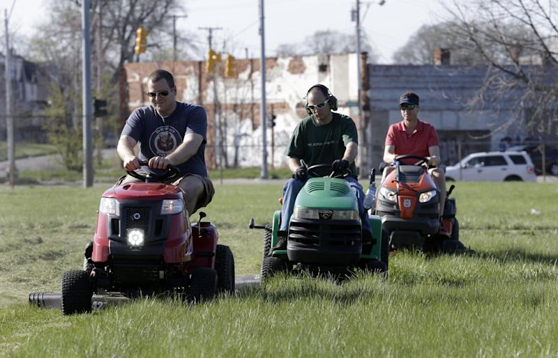 Mower Gang members Nathan Labadie, of Commerce Township, from left, Andrew Haig, of Birmingham, and Darton Case, of Birmingham mow at Duweke Park in Detroit, Wednesday May 1, 2013. The Mower Gang, a group of volunteer lawn mower riders, adopt parks beginning in the spring and keep them free of high-grass throughout the summer. (AP Photo/Paul Sancya)