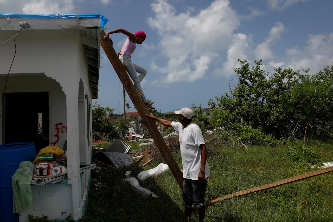 <p>Devon Warner and his daughter Che Niesha climb off of a ladder from the roof of a damaged home at Codrington on the island of Barbuda just after a month after Hurricane Irma struck the Caribbean islands of Antigua and Barbuda, October 7, 2017. REUTERS/Shannon Stapleton </p>