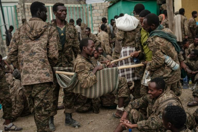 Captured Ethiopian troops carry a soldier on a makeshift stretcher to a treatment centre in Mekele, the Tigrayan capital, on July 2