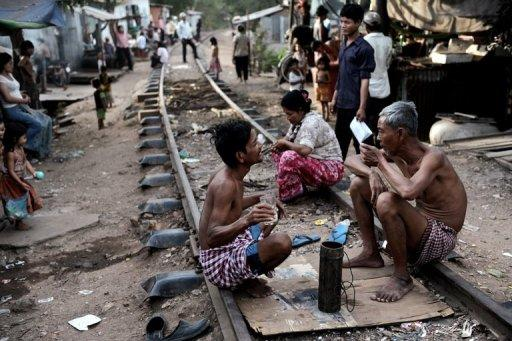 People sit along railroad tracks outside their shanty homes in the Boeng Kak slum area of Phnom Penh