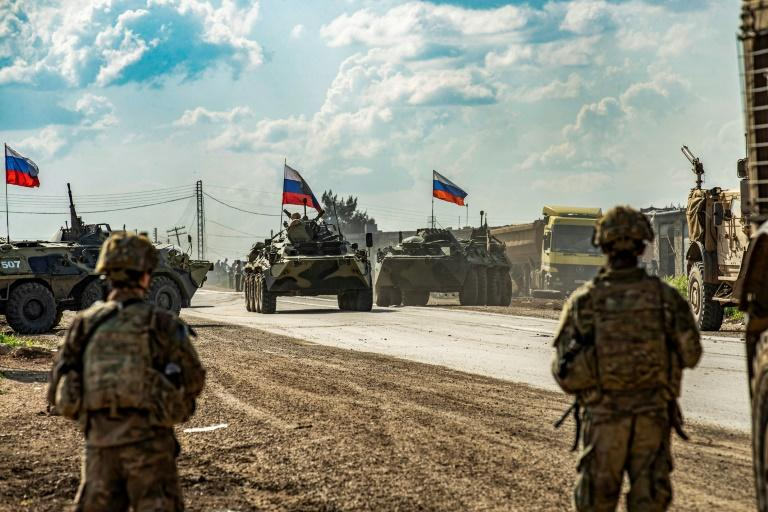 US soldiers stand along a road across from Russian military armored personnel carriers near the village of Tannuriyah in Syria's northeastern Hasakah province on May 2, 2020