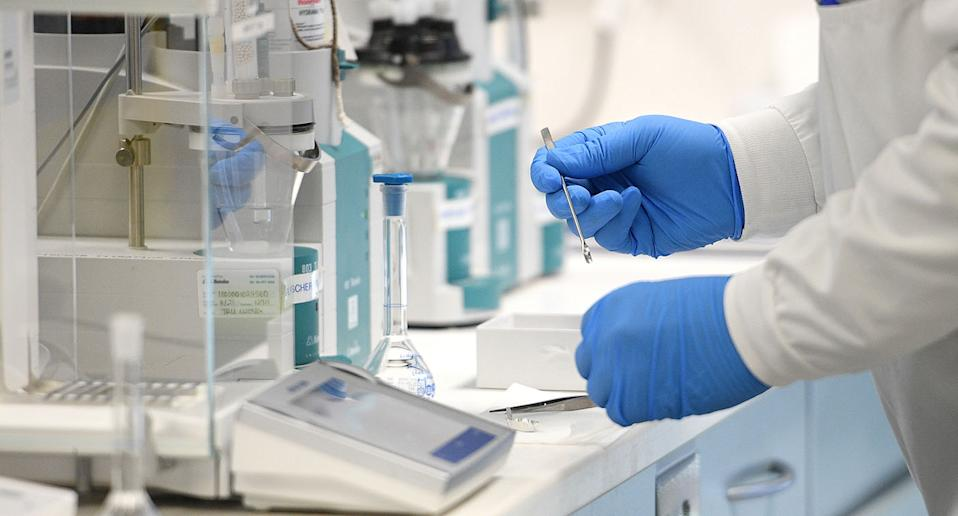 Researchers hands in lab shown working on vaccine.