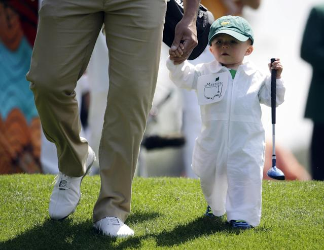 Scott Stallings walks with his son Finn after teeing off on the first hole during the par three competition at the Masters golf tournament Wednesday, April 9, 2014, in Augusta, Ga. (AP Photo/Darron Cummings)