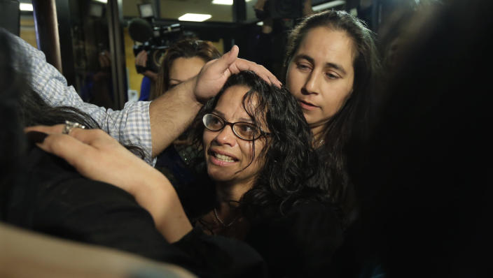 Elizabeth Ramirez, center, is greeted by family after she, Cassandra Rivera and Kristie Mayhugh were released from the Bexar County Jail, Monday, Nov. 18, 2013, in San Antonio. The San Antonio women imprisoned for sexually assaulting two girls in 1994 were allowed to walk free after a judge agreed that their convictions were tainted by faulty witness testimony. (AP Photo/Eric Gay)