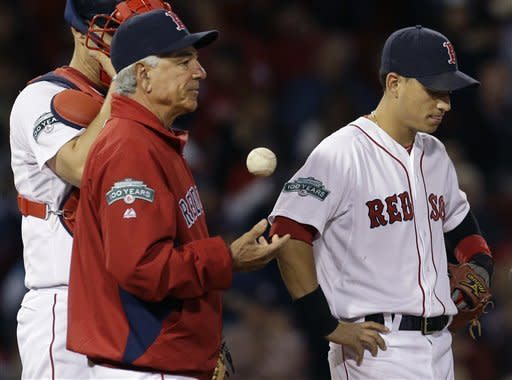 Boston Red Sox manager Bobby Valentine tosses a baseball while he and shortstop Jose Iglesias, right, and catcher Ryan Lavarnway, partially hidden, wait on the mound for relief pitcher Andrew Miller in the eighth inning against the Tampa Bay Rays at Fenway Park in Boston, Tuesday, Sept. 25, 2012. The Rays won 5-2. (AP Photo/Elise Amendola)