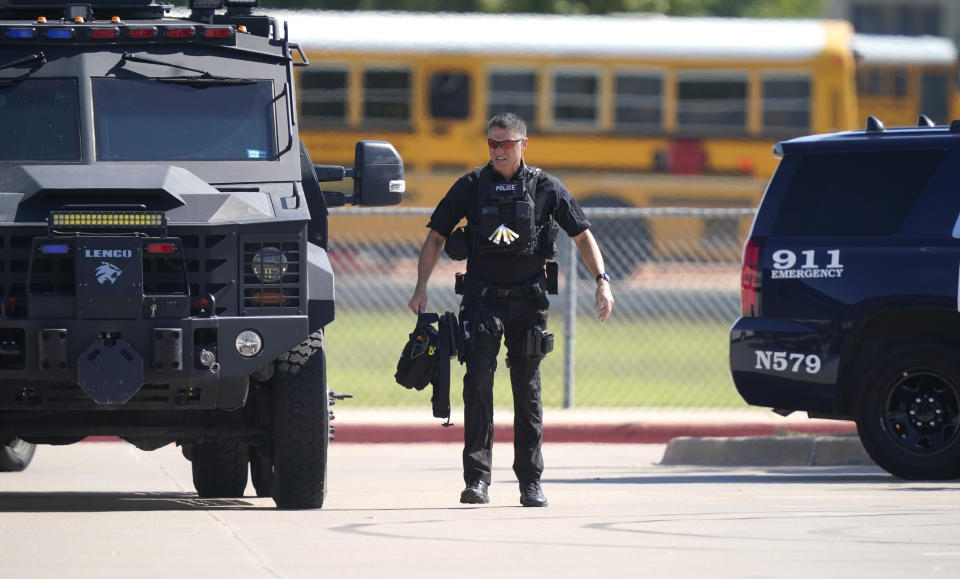 A law enforcement officer walks in the parking lot of Timberview High School after a shooting inside on Wednesday. Source: AP