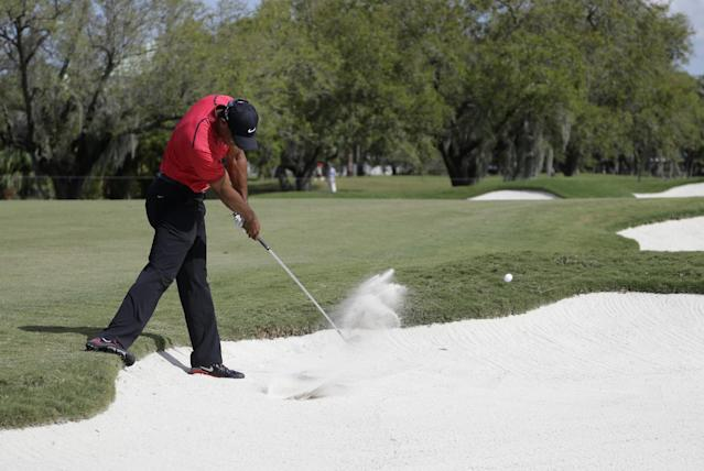 Tiger Woods hits from a bunker on the sixth hole during the final round of the Cadillac Championship golf tournament Sunday, March 9, 2014, in Doral, Fla. Woods' back flared up as a result of this shot. He would up with a 78, his highest score ever on Sunday, and for the first time fialed to make a single birdie in the final round. (AP Photo/Lynne Sladky)