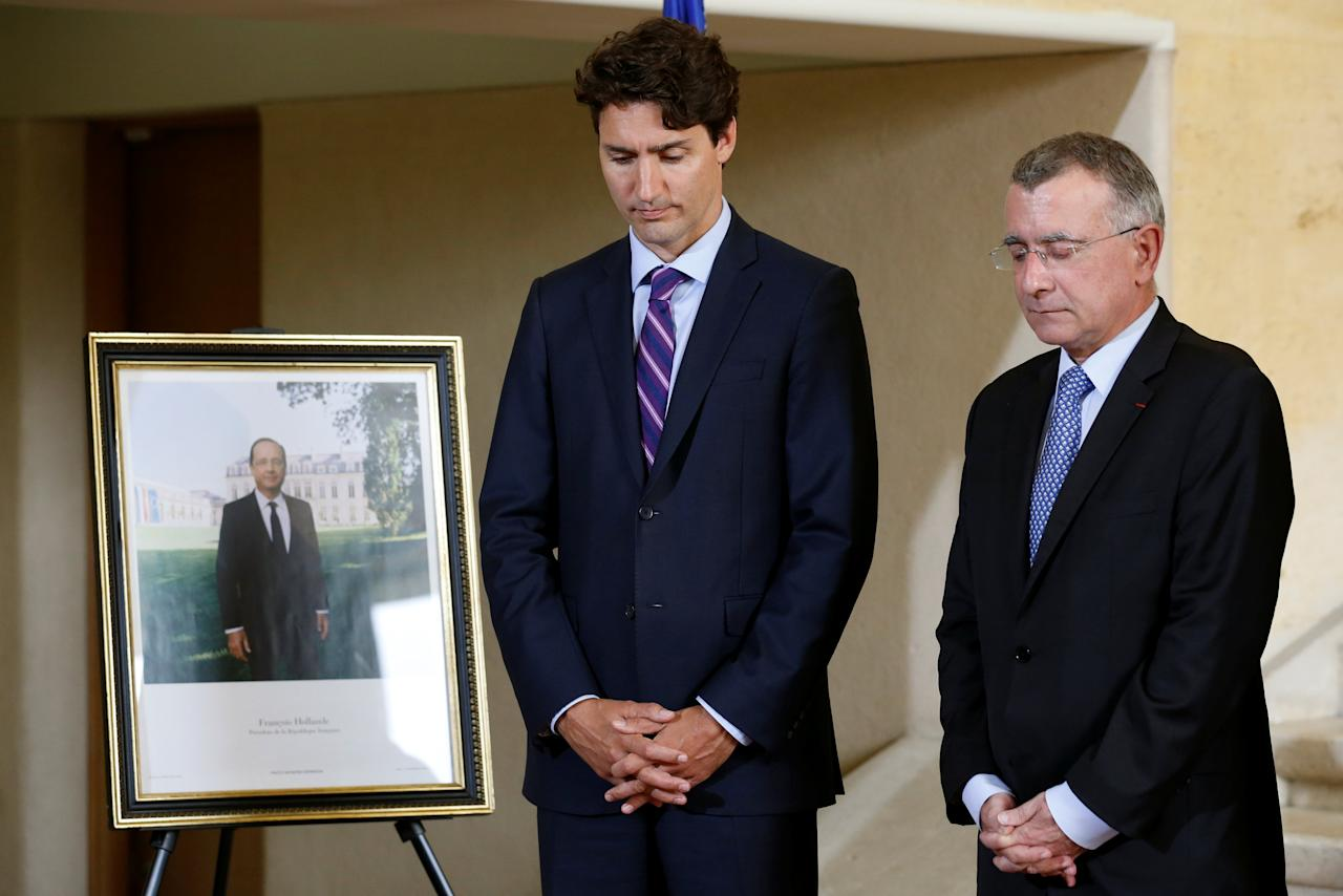 Canada's Prime Minister Justin Trudeau (L) takes part in a moment of silence with French Ambassador to Canada Nicolas Chapuis after signing a book of condolences for the victims of the Bastille Day truck attack in Nice, at the French embassy in Ottawa, Ontario, Canada, July 18, 2016. REUTERS/Chris Wattie   TPX IMAGES OF THE DAY
