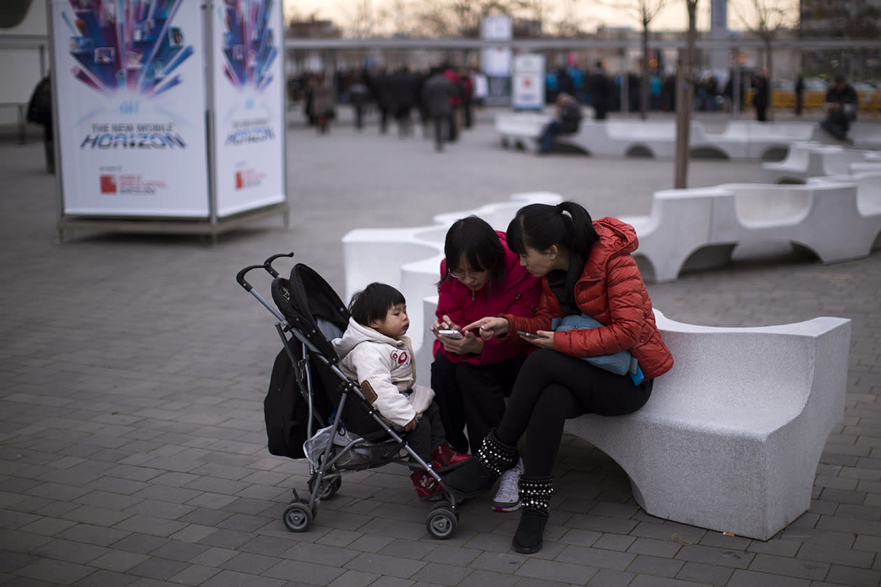 Visitors use their mobile phones during the inauguration of the Mobile World Congress.