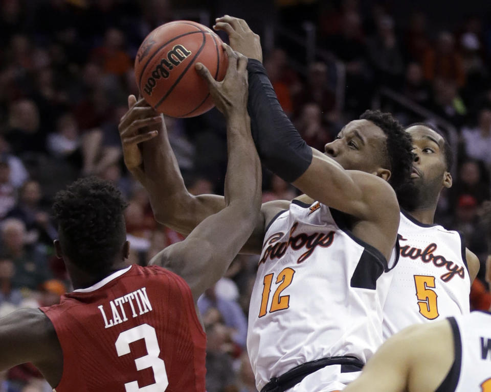 Oklahoma State forward Cameron McGriff (12) and Oklahoma forward Khadeem Lattin (3) reach for a rebound during the second half of an NCAA college basketball game in first round of the Big 12 men's tournament in Kansas City, Mo., Wednesday, March 7, 2018. Oklahoma State defeated Oklahoma 71-60. (AP Photo/Orlin Wagner)