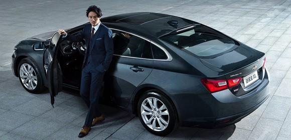 A man in a suit stands next to a dark gray Chevrolet Malibu XL, a large midsize sedan.