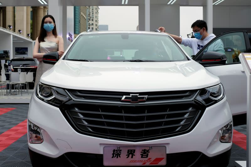 Model stands next to a Chevrolet vehicle at a sales event in Shanghai