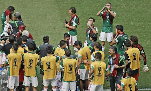 Mexican players consume drinks during a cooling break of the World Cup round of 16 soccer match between the Netherlands and Mexico at the Arena Castelao in Fortaleza, Brazil, Sunday, June 29, 2014. (AP Photo/Themba Hadebe)