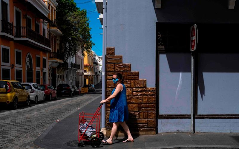 A woman wearing a protective mask pushes a shipping cart on a sidewalk in Old San Juan, Puerto Rico  - RICARDO ARDUENGO/AFP