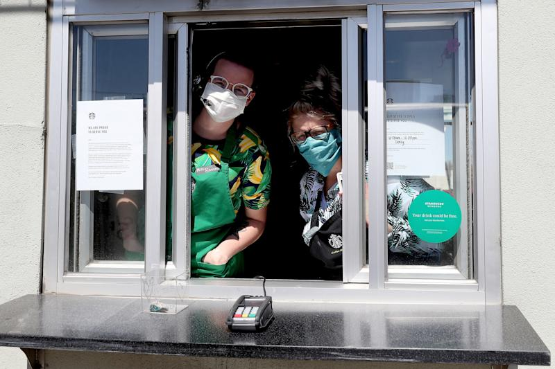 EDGEWATER, COLORADO - APRIL 07: Starbucks employees wear a mask while working the drive-thru window on April 07, 2020 in Edgewater, Colorado. Starting today Starbucks will require all employees to wear facemasks at work. The chain has closed in-store cafes however drive-thru locations remain open. (Photo by Matthew Stockman/Getty Images)