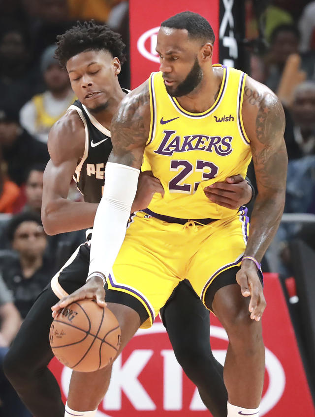 Atlanta Hawks forward Cam Reddish, left, grabs Los Angeles Lakers' LeBron James (23) during the first half of an NBA basketball game Sunday, Dec. 15, 2019, in Atlanta. (Curtis Compton/Atlanta Journal-Constitution via AP)