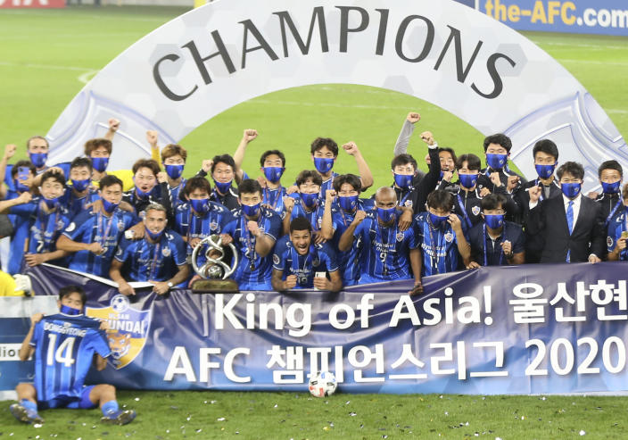 Ulsan Hyundai's players pose with a trophy after the AFC Champions League final match against Persepolis in Al Wakrah, Qatar, Saturday, Dec. 19, 2020. (AP Photo/Hussein Sayed)