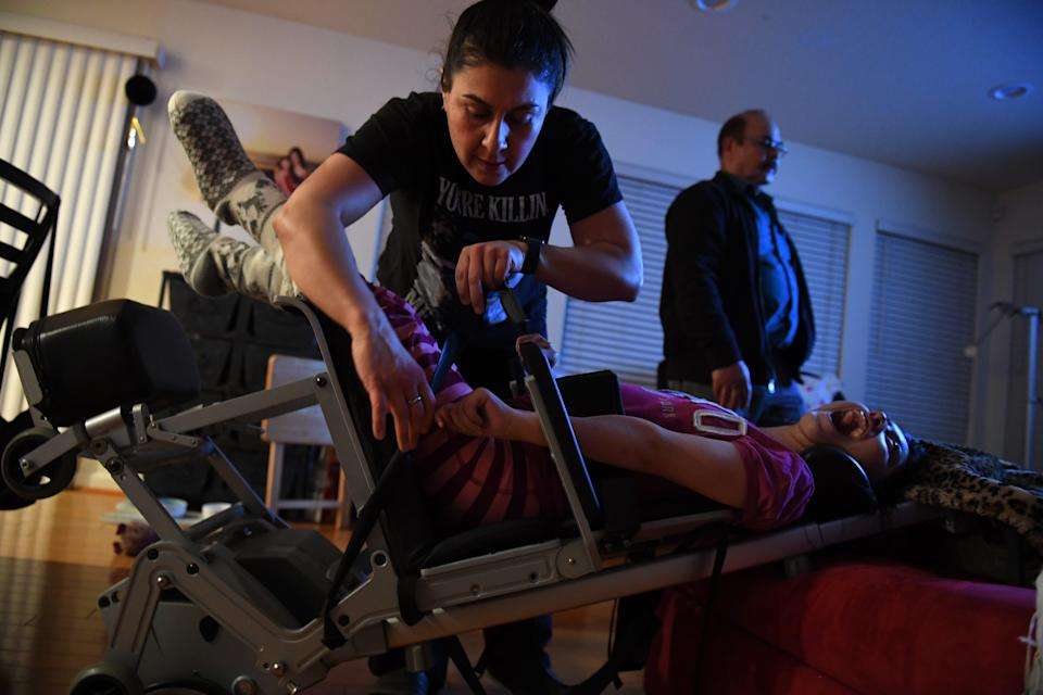 Maribel Landeros straps in her daughter Karizma into her chair one night at her Salinas, California, home. Maribel's father stands behind her as a TV plays.