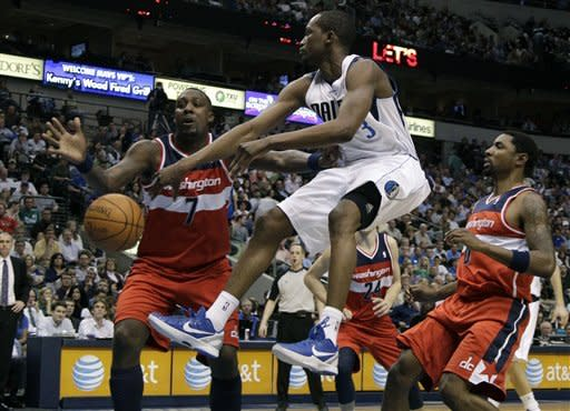 Dallas Mavericks guard Rodrigue Beaubois, center, of Guadeloupe, passes as Washington Wizards' Andray Blatche (7) and Roger Mason, right, defend during the first half of an NBA basketball game on Tuesday, March 13, 2012, in Dallas. (AP Photo/Tony Gutierrez)
