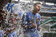Philadelphia Phillies' Brad Miller is doused by teammates in the dugout after hitting a grand slam in the eighth inning to give the Phillies an 11-8 win over the Washington Nationals in the second baseball game of a doubleheader Thursday, July 29, 2021, in Philadelphia. (AP Photo/Laurence Kesterson)