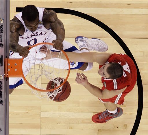 Kansas forward Thomas Robinson (0) slam dunks over Ohio State guard Aaron Craft (4) during the second half of an NCAA Final Four semifinal college basketball tournament game Saturday, March 31, 2012, in New Orleans. (AP Photo/Mark Humphrey)