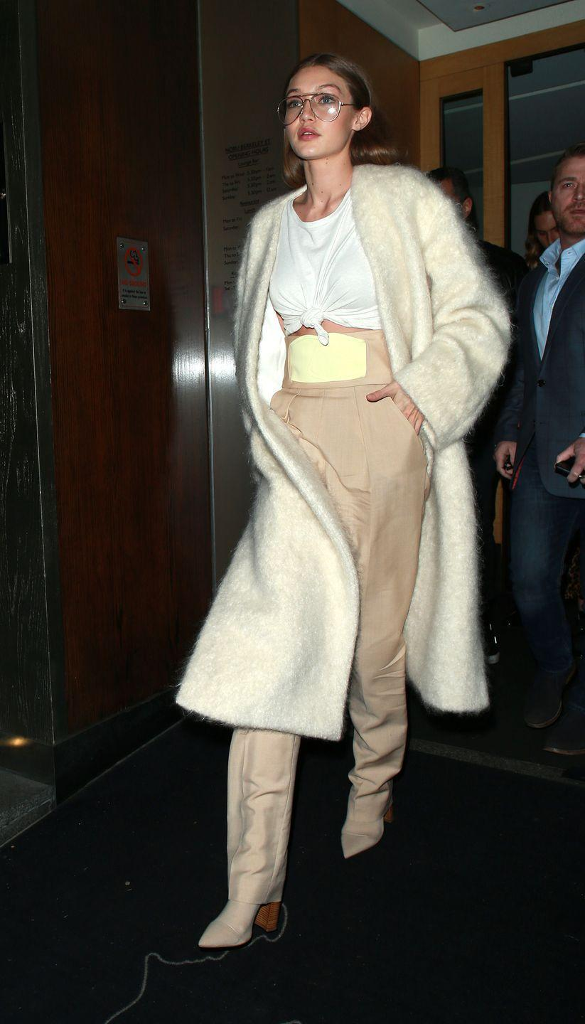 <p>In ultra high-waisted nude trousers, a cinched white tee, cream fur coat, ankle boots and wire-rim glasses while out in London</p>