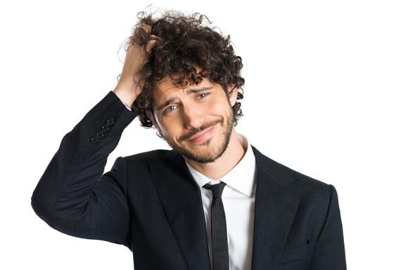 A confused millennial in a suit scratching the top of his head.