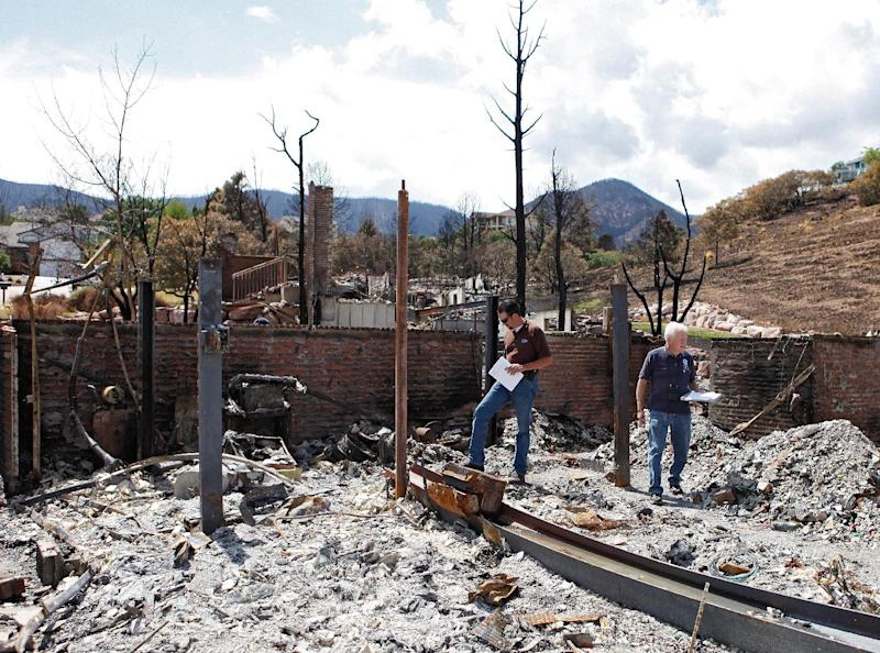 Members of FEMA walk through the ashes of a burned home in Colorado Springs, Colo., on Monday, July 9, 2012. Members of FEMA, the SBA and Colorado's Disaster Office assessed damages in the area burned by the Waldo Canyon wildfire. (AP Photo/Ed Andrieski)