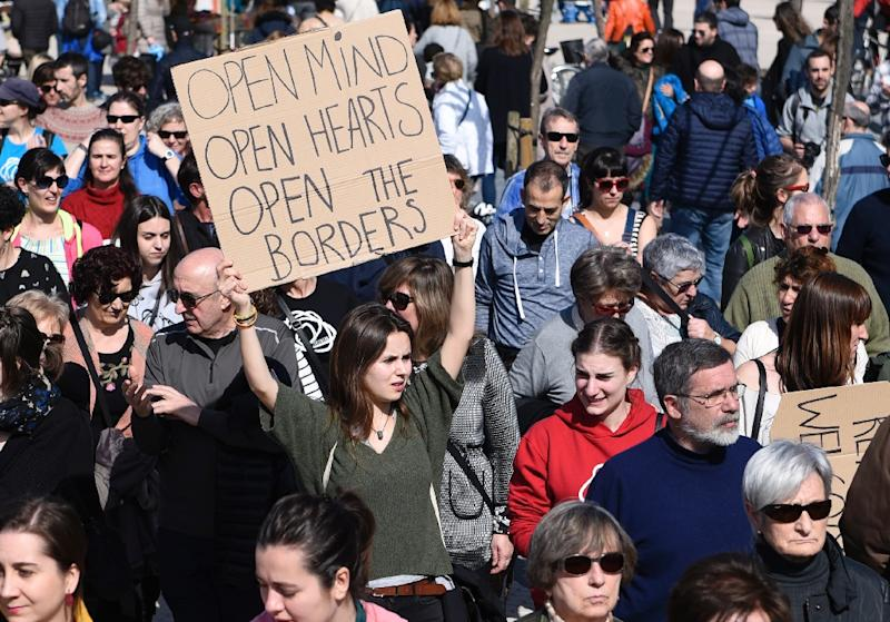 People hold placards during a pro-refugee demonstration in the Spanish Basque city of San Sebastian on February 26, 2017 as Spain has resettled only 1,100 of the 16,200 refugees it pledged to take in within two years