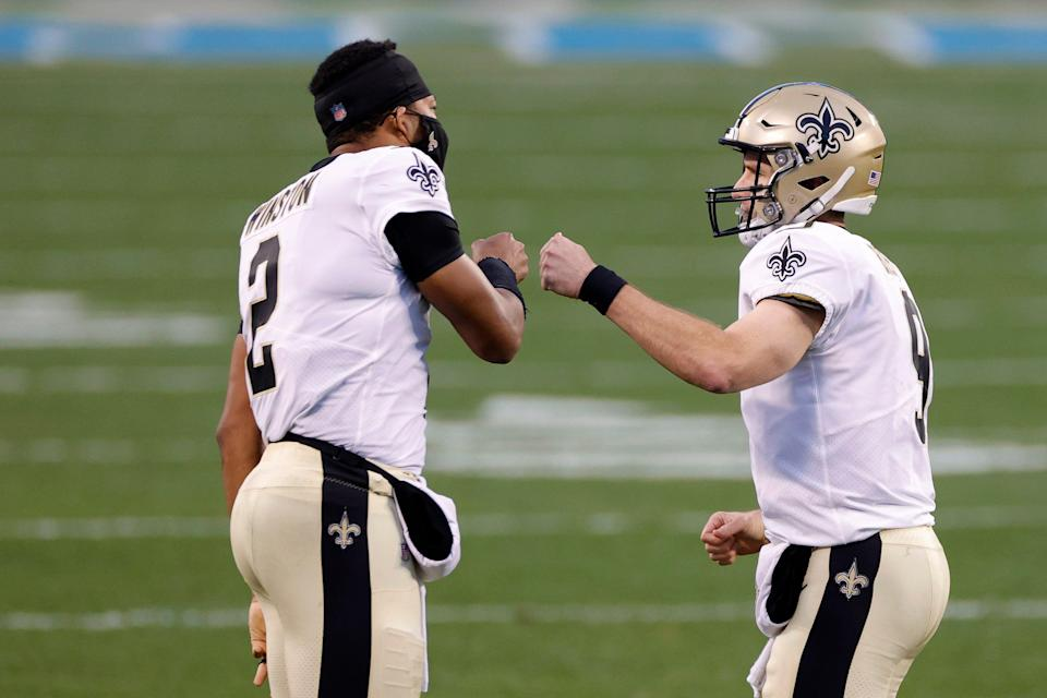 Quarterback Drew Brees of the New Orleans Saints celebrates with teammate quarterback Jameis Winston following a touchdown pass during the first quarter of their game against the Carolina Panthers at Bank of America Stadium on January 03, 2021 in Charlotte, North Carolina.