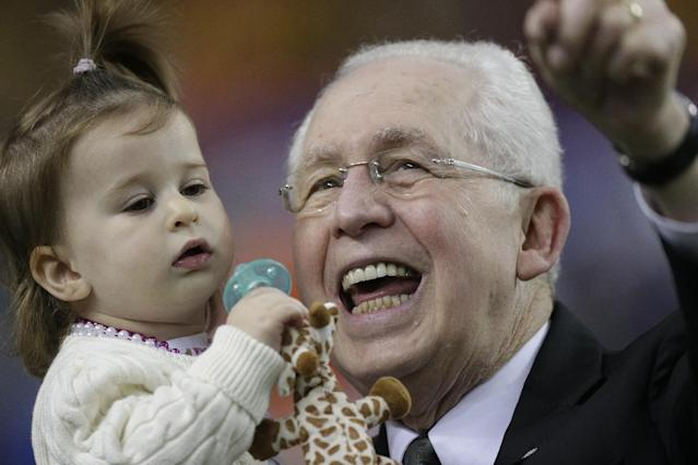 SEC Commissioner Mike Slive holds his two-year-old granddaughter Abigail before the first half of the Southeastern Conference NCAA football championship game between the Auburn and the Missouri, Saturday, Dec. 7, 2013, in Atlanta. (AP Photo/Dave Martin)
