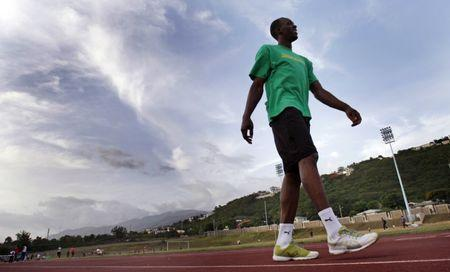 World record holder and Olympic Champion Usian Bolt stretches on the warm-up track adjacent the National Stadium prior to competing at the Jamaican Athletics National Championship in Kingston, Jamaica June 27, 2009. REUTERS/Hans Deryk