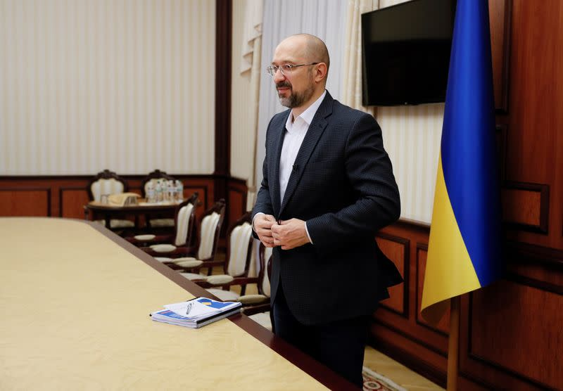 Ukraine's Prime Minister Shmygal buttons his jacket after an interview in Kiev