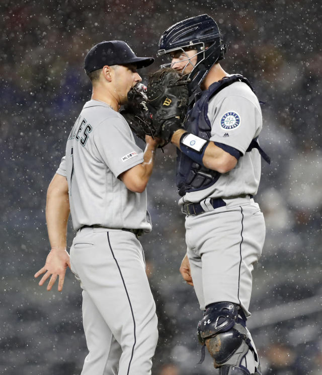 Seattle Mariners starting pitcher Marco Gonzales, left, talks to catcher Tom Murphy (2) as rain falls during the seventh inning of the team's baseball game against the New York Yankees, Tuesday, May 7, 2019, in New York. (AP Photo/Kathy Willens)