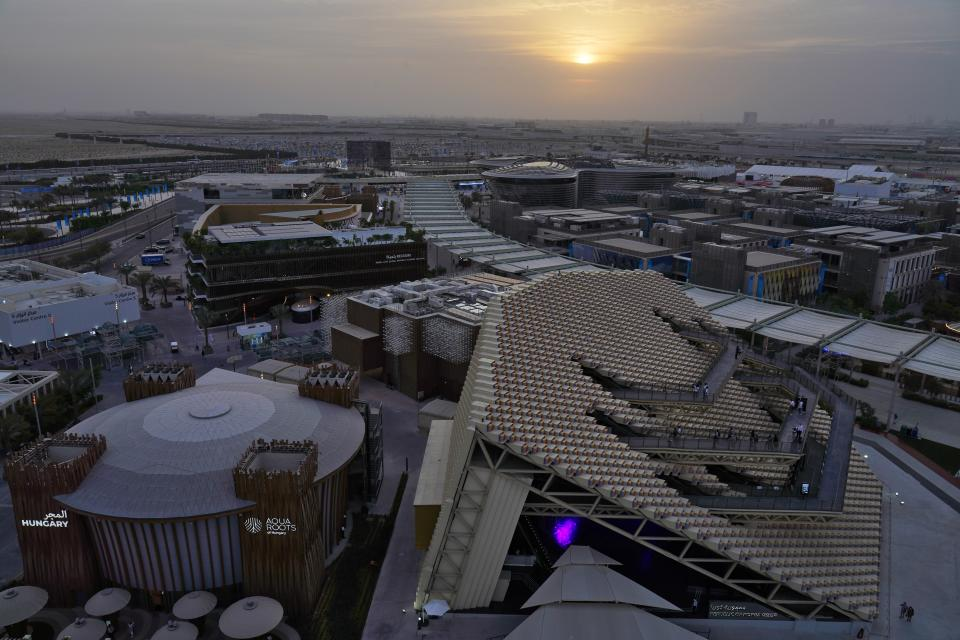 The South Korea and Hungary pavilions are seen at sunset at Expo 2020, in Dubai, United Arab Emirates, Sunday, Oct. 3, 2021. (AP Photo/Jon Gambrell)