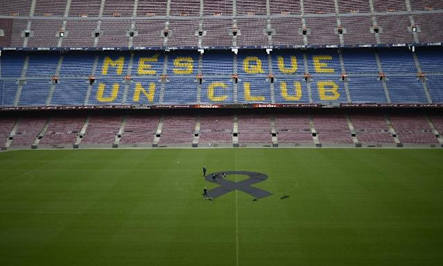 "FC Barcelona's employees place a black sash mid-field in respect to late former FC Barcelona's coach Tito Vilanova at Camp Nou Stadium in Barcelona, Spain, Saturday, April 26, 2014. FC Barcelona announced on their web page Friday April 25, 2014, that Vilanova has died Friday following a long battle with throat cancer. He was 45. The sign on stands reads ""More than a Club"". (AP Photo/Manu Fernandez)"