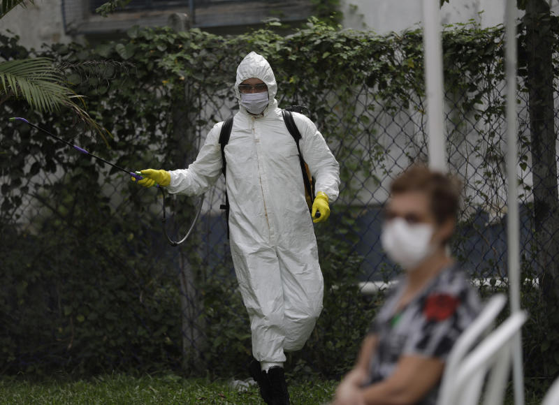 An army soldier wearing protection gear disinfects the Marechal Hermes Urgent Care Unit, amid the new coronavirus pandemic in Rio de Janeiro, Brazil, Wednesday, May 6, 2020. (AP Photo/Silvia Izquierdo)