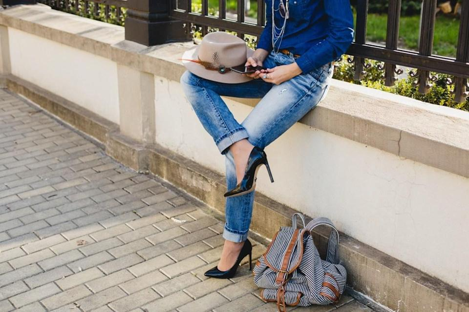 woman, hands holding a phone, denim shirt and jeans, high heel shoes, hat, backpack