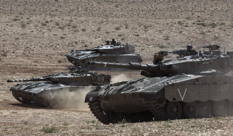 Israeli army tanks participate in a drill near Revivim southern Israel, Thursday, March 7, 2013. On a dusty field in Israel's southern desert, the military is gearing up for the next battle against a familiar foe: Hezbollah guerrillas in Lebanon. As the Syrian civil war intensifies on Israel's northern doorstep, military planners are growing increasingly jittery that the fighting could spill over into Israel, potentially dragging Hezbollah into the fray. (AP Photo/Sebastian Scheiner)