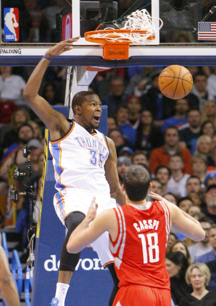 Oklahoma City Thunder forward Kevin Durant (35) dunks in front of Houston Rockets forward Omri Casspi (18) during the first quarter of an NBA basketball game, Sunday, Dec. 29, 2013, in Oklahoma City. (AP Photo/Alonzo Adams)