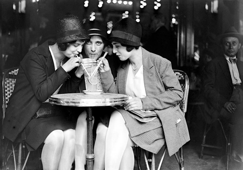 """A classic vintage Paris image: Young women decked out in 1920s fashion, sharing a drink <a href=""""https://www.cntraveler.com/gallery/best-cafes-and-coffee-shops-in-paris?mbid=synd_yahoo_rss"""" rel=""""nofollow noopener"""" target=""""_blank"""" data-ylk=""""slk:in a café"""" class=""""link rapid-noclick-resp"""">in a café</a> during the heat wave of July 1929."""