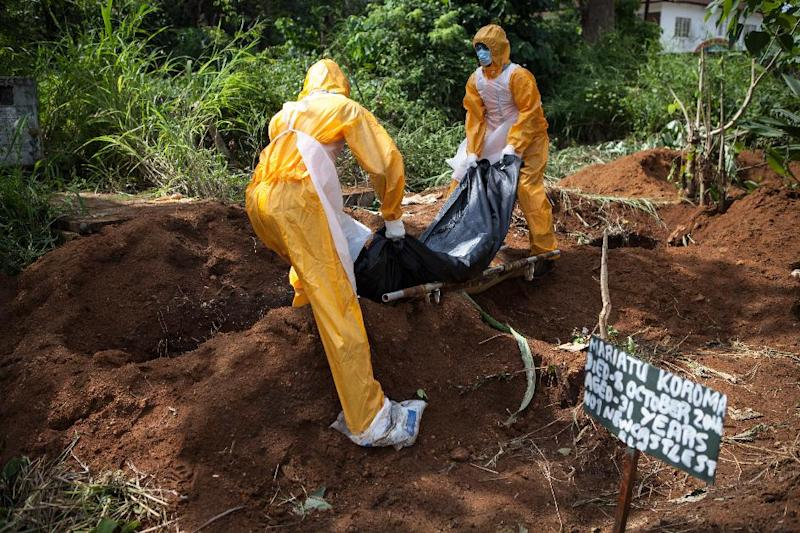 A team of funeral agents specialised in the burial of victims of the Ebola virus put a body in a grave at the Fing Tom cemetery in Freetown, on October 10, 2014 (AFP Photo/Florian Plaucheur)