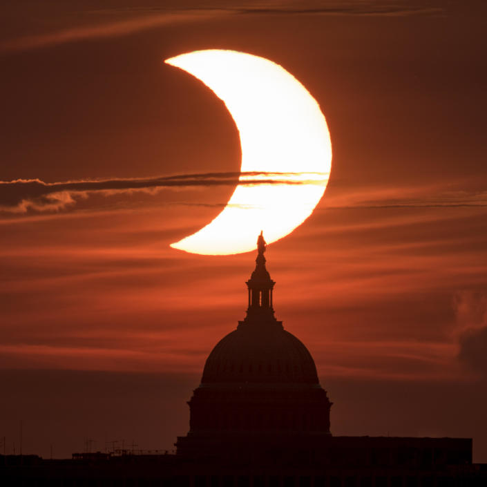 In this handout image provided by NASA, a partial solar eclipse is seen as the sun rises behind the Capitol Building on June 10, 2021, seen from Arlington, Virginia. / Credit: Bill Ingalls/NASA via Getty Images